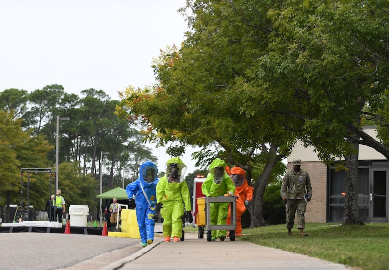 Members of the Keesler fire department, bioenvironmental and emergency management make their way to the scene for testing a simulated biological agent during the Anti-Terrorism, Force Protection Condition and Chemical, Biological, Radiological, Nuclear and high-yield Explosives training exercise near the Live Oak Dining Facility at Keesler Air Force Base, Mississippi, Oct. 24, 2019. The exercise scenario simulated a gym bag with ricin found by Keesler personnel who alerted first responders. The exercise was conducted to evaluate the mission readiness and security of Keesler. (U.S. Air Force photo by Kemberly Groue)