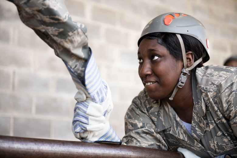 An Air Force Junior Reserve Officer Training Corps cadet from Robert E. Lee High School takes her teammates hand while balancing across an obstacle a part of the Officer Training School Leadership Reaction Course, Oct. 24, 2019, Maxwell Air Force Base, Alabama. The LRC is comprised of a series of obstacles that are designed to foster teamwork, communication and critical thinking. (U.S. Air Force photo by Senior Airman Alexa Culbert)