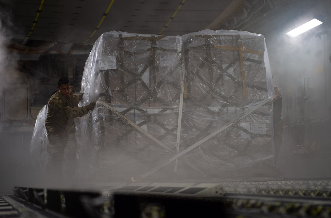 U.S Air Force Staff Sgt. Marcello Moffat, 8th Airlift Squadron loadmaster, helps push a pallet containing rice off a C-17 Globemaster III assigned to the 62nd Airlift Wing, Joint Base Lewis-McChord, Wash., at Soto Cano Air Base, Honduras, Oct. 24, 2019. Almost $120,000 worth of rice was donated to help feed Honduran men, women and children. (U.S Air Force photo by Senior Airman Tryphena Mayhugh)