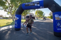 Major Ernest Robinson, Operations officer, finishes the Domestic Violence Awareness Run/Walk strong, carrying his 9-year-old daughter Maegon across the finish line aboard Marine Corps Logistics Base Barstow, Calif., Oct. 23. The event raises awareness of and support for victims and survivors of domestic violence in a fun, healthy, family-friendly manner.