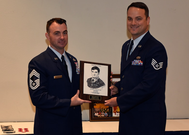 U.S. Air Force Chief Master Sgt. Michael Padgett, 17th Mission Support Group superintendent, presents the John L. Levitow Award to Staff Sgt. Patrick Berger, 17th Contracting Squadron contracting specialist, at the event center on Goodfellow Air Force Base, Texas, Oct. 24, 2019. The John L. Levitow Award is the highest award possible in professional military education, it is based upon all performance tasks, peer stratifications, and the capstone exercise. (U.S. Air Force photo by Airman 1st Class Ethan Sherwood/Released)