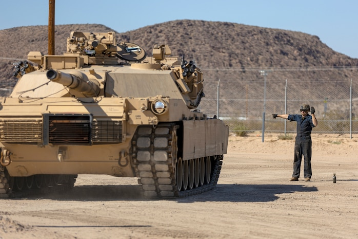 Corporal Melvin Golden, motor vehicle operator, ground guides a M1A1 Abrams Main Battle Tank during offload procedures of Second Marine Division's assets aboard the Yermo Annex of Marine Corps Logistics Base Barstow, Calif., Sept. 27. The Marine vehicles will be transported by truck to Marine Corps Air-Ground Combat Center, 29 Palms, Calif.,to engage in a four day training exercise.