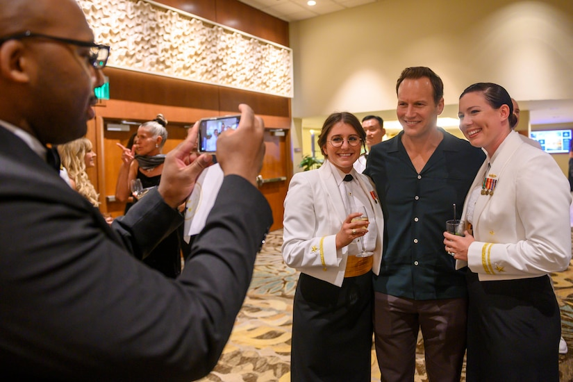 A man takes a cellphone photo of actor Patrick Wilson standing between two female sailors in dress uniform at a gala.