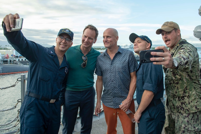 Actors Patrick Wilson and Woody Harrelson pose on the deck of a ship to get selfies with three sailors.