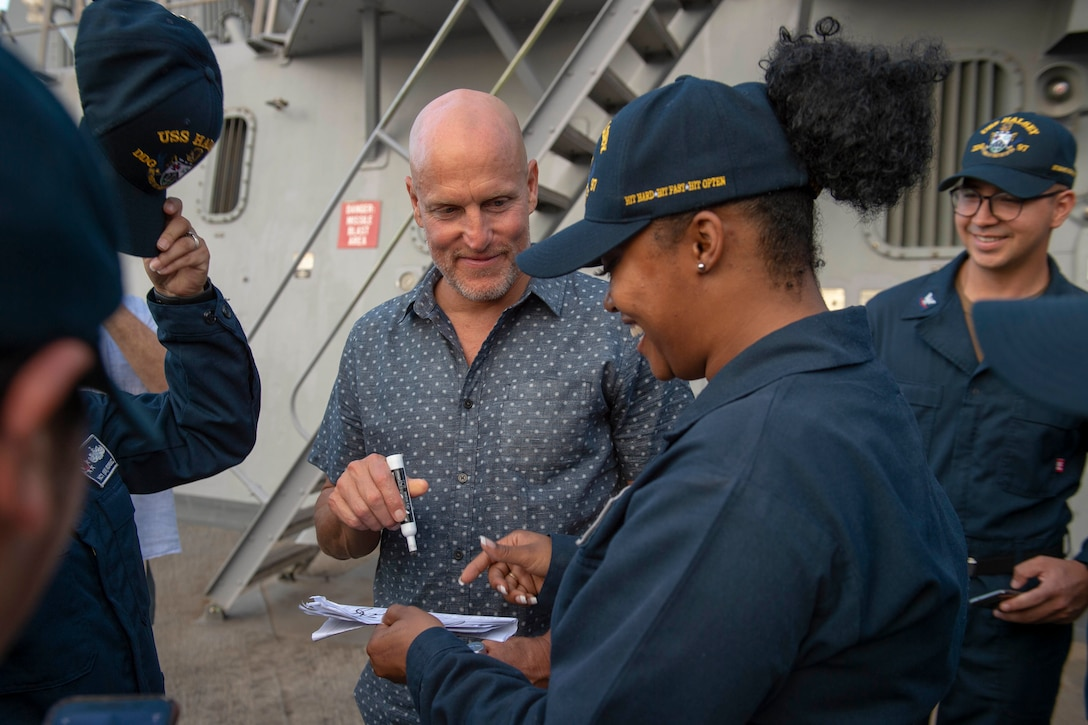 Actor Woody Harrelson signs an autograph for a female sailor as other sailors smile beside her.