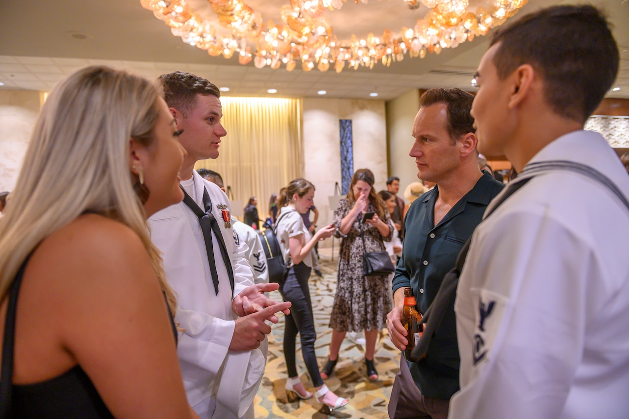 Two sailors in dress uniform and a woman in a dress speak with actor Patrick Wilson while standing in a circle at a gala.