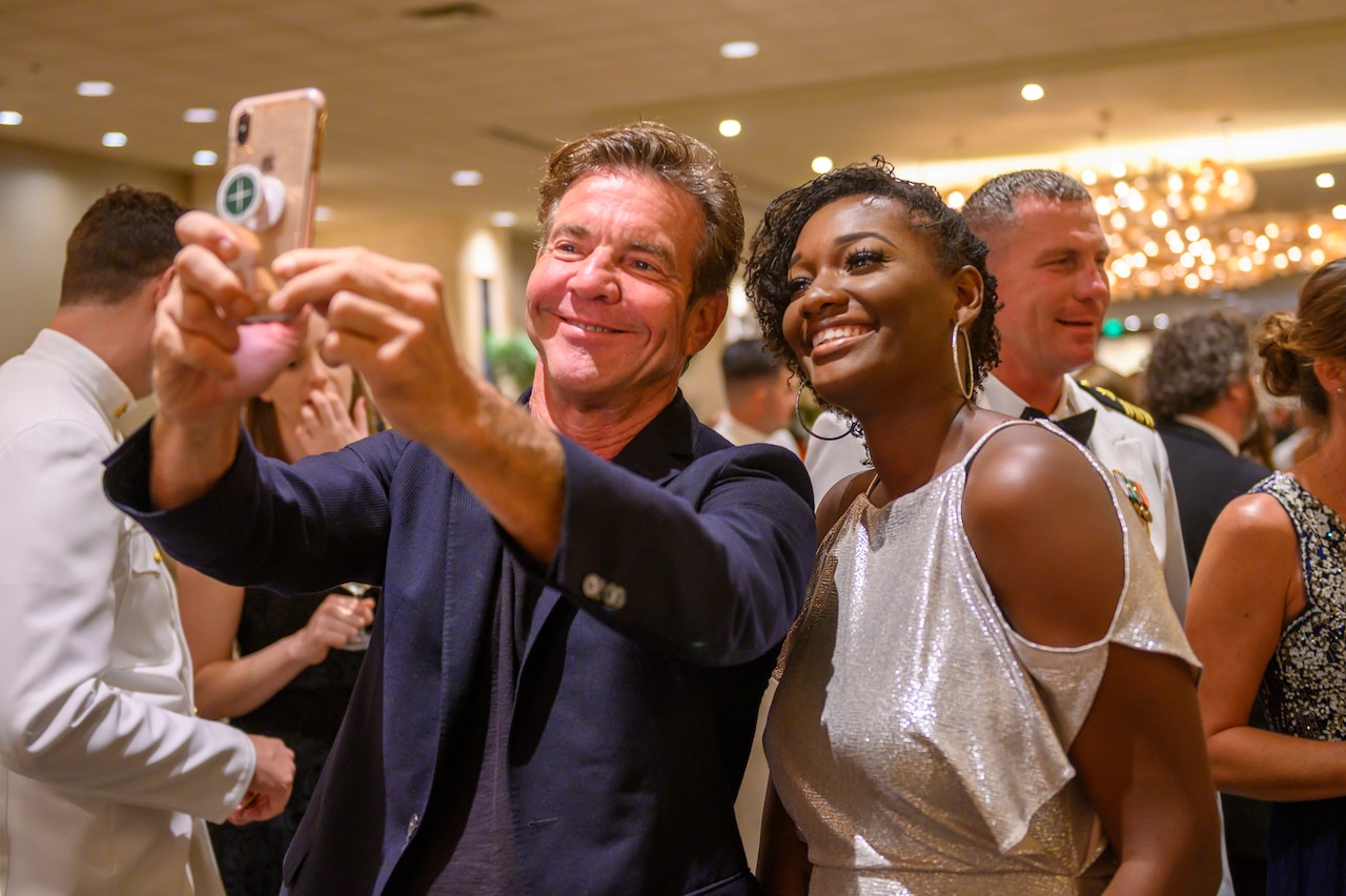 Actor Dennis Quaid holds out a cellphone to take a selfie with a woman wearing a fancy dress. Others mill around behind them.