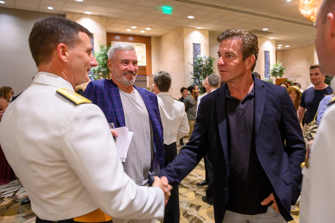 Actor Dennis Quaid shakes the hand of a Navy admiral while a film director and another sailor stand by.