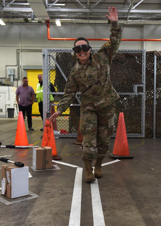 """Col. Carol Miller, 100th Mission Support Group commander, wears """"drunk goggles"""" while attempting to walk a straight line at the end of an obstacle course during a 100th Logistics Readiness Squadron safety event at RAF Mildenhall, England, Oct. 11, 2019. Airmen and civilians put together the event which emphasized the dangers or drunk driving and showed the brutal consequences that can happen as a result. The 100th LRS Airmen and civilians worked together to put together an event focusing on the dangers of drunk driving and its consequences. (U.S. Air Force photo by Karen Abeyasekere)"""