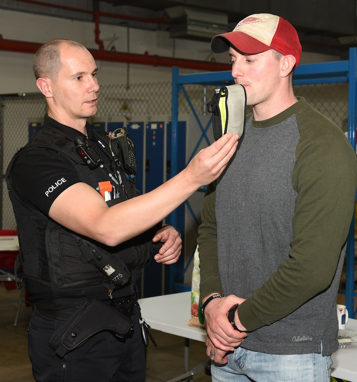 Police Constable Simon Myall, Suffolk Police, breathalyzes an 100th Logistics Readiness Squadron Airman during a controlled drinking experiment as part of a safety awareness event at RAF Mildenhall, Oct. 11, 2019. The event was to focus on the dangers and show consequences of drunk driving, while at the same time promote safe practices for 100th LRS Airmen and civilians in a way other than slide shows.  (U.S. Air Force photo by Karen Abeyasekere)