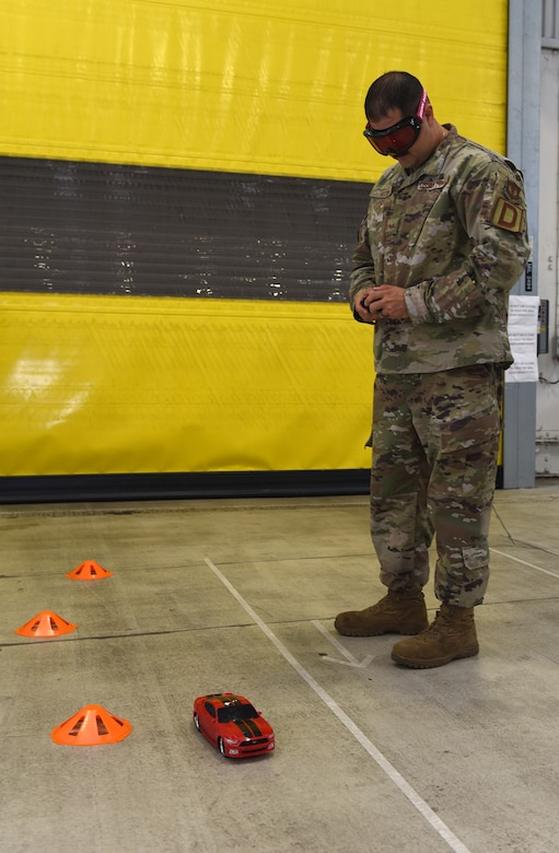 """An Airman from the 100th Logistics Readiness Squadron attempts to steer a remote-control car through a mini course while wearing """"drunk goggles"""" at an event to highlight the dangers of drunk driving at RAF Mildenhall, England, Oct. 11, 2019. Members of Suffolk Police, along with the 48th Medical Operations Squadron Alcohol and Drug Prevention and Treatment Program, attended the safety event to show the effects alcohol has on motor skills. (U.S. Air Force photo by Karen Abeyasekere)"""