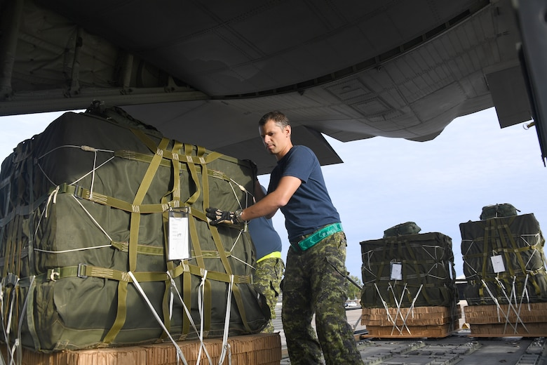 Royal Canadian Air Force loadmasters push cargo onto a C-130 aircraft during exercise Green Flag Little Rock, Oct. 24, 2019, Alexandria International Airport, Louisiana. The exercise also gave Airmen a unique opportunity to enhance partnerships with joint and allied partners. (U.S. Air Force photo by Tech. Sgt. Liliana Moreno)