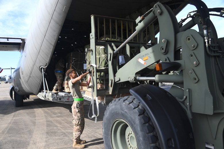 U.S. Air Force Airman 1st Class Dominitrius Stribling, 321st Contingency Response Squadron aerial porter, secures cargo being loaded onto a Swedish Air Force C-130 aircraft during exercise Green Flag Little Rock, Oct. 24, 2019, Alexandria International Airport, Louisiana. During the exercise the team loaded and downloaded tactical vehicles, airdrop bundles, along with a variety of other pallets to support the Army. (U.S. Air Force photo by Tech. Sgt. Liliana Moreno)