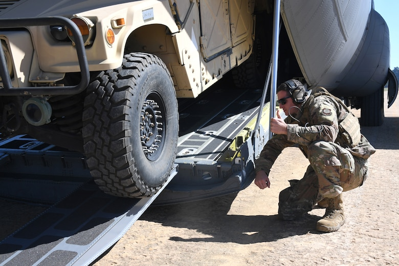 U.S. Air Force Staff Sgt. Christopher Hayes, 621st Contingency Response Support Squadron aircraft maintenance, checks aircraft clearance while loading cargo inside a C-130 Hercules aircraft at the Geronimo Landing Zone during exercise Green Flag Little Rock, Oct. 23, 2019, Fort Polk, Louisiana. During the exercise the team loaded and downloaded tactical vehicles, airdrop bundles, along with a variety of other pallets to support the Army. (U.S. Air Force photo by Tech. Sgt. Liliana Moreno)