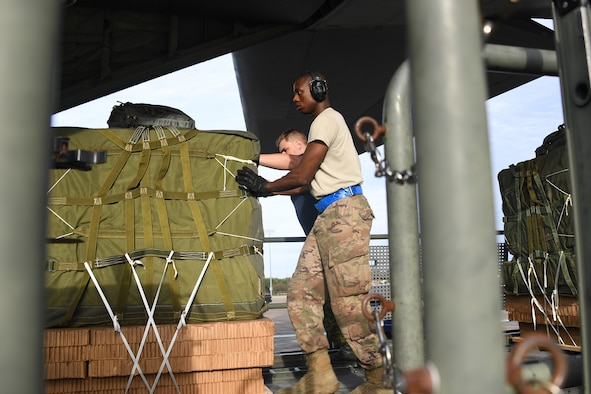 U.S. Air Force Airman 1st Class Ernest Washington, 821st Contingency Response Support Squadron aerial porter, pushes cargo onto a Royal Canadian Air Force C-130 aircraft during exercise Green Flag Little Rock, Oct. 24, 2019, Alexandria International Airport, Louisiana. During the exercise the team loaded and downloaded tactical vehicles, airdrop bundles, along with a variety of other pallets to support the Army. (U.S. Air Force photo by Tech. Sgt. Liliana Moreno)