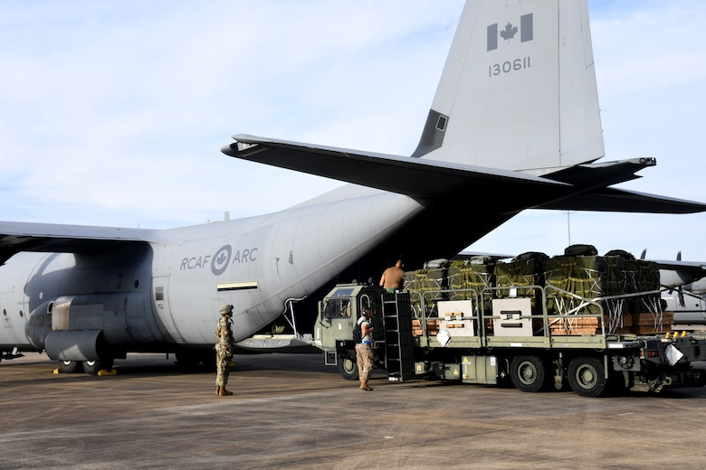U.S. Air Force aerial porters from the 621st Contingency Response Group load cargo onto a Royal Canadian Air Force C-130 aircraft during exercise Green Flag Little Rock, Oct. 24, 2019, Alexandria International Airport, Louisiana. During the exercise the team loaded and downloaded tactical vehicles, airdrop bundles, along with a variety of other pallets to support the Army. (U.S. Air Force photo by Tech. Sgt. Liliana Moreno)