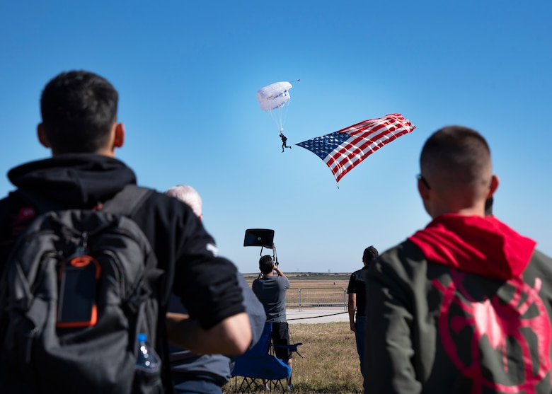 Event goers watch a U.S. Air Force Academy Wings of Blue parachute team member at the Sheppard Air Force Base Guardians of Freedom Open House and Air Show at Sheppard AFB, Texas, Oct. 27, 2019. The open house and air show is a chance for Sheppard to show and communicate the Air Force's mission as well as Sheppard's specific mission of training, developing and inspiring the next generation of Air Force warriors. (U.S. Air Force photo by Airman 1st Class Pedro Tenorio)