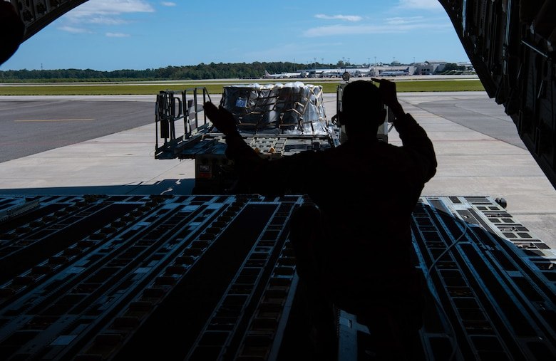 U.S. Air Force Staff Sgt. Marcello Moffat, 8th Airlift Squadron (AS) loadmaster, marshals a 1,000-pound loader toward a C-17 Globemaster III assigned to the 62nd Airlift Wing, Joint Base Lewis-McChord, Wash., at Altus Air Force Base, Okla., Oct. 24, 2019. Moffat and other 8th AS Airmen delivered more than 83,000 pounds of rice to Honduras for a humanitarian mission. (U.S Air Force photo by Senior Airman Tryphena Mayhugh)