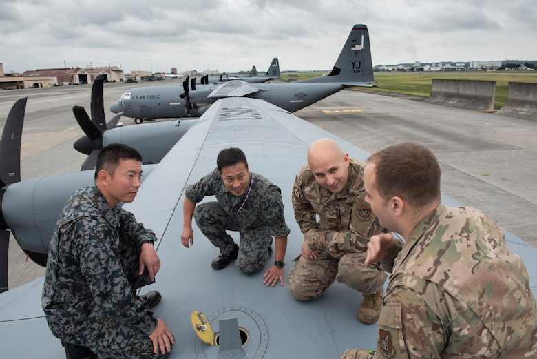 Staff Sgt. Joseph Crinite, 374th Aircraft Maintenance Squadron C-130J Hercules communication and navigation craftsman, shows a dry bay panel on top of a C-130J Super Hercules to members from the Japan Air Self-Defense Force during a Bilateral Exchange Program, Oct. 24, 2019, at Yokota Air Base, Japan.