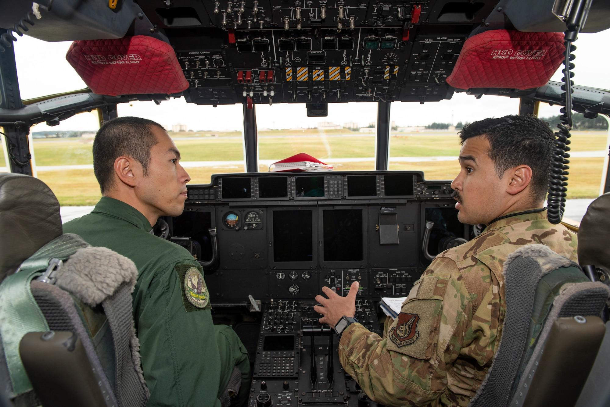 Staff Sgt. Hector Frietze, 36th Airlift Squadron loadmaster, explains how they perform pre-flight inspections inside a C-130J Super Hercules to Koku-Jieitai Tech. Sgt. Hideki Tanaka, 403rd Tactical Airlift Squadron loadmaster assigned with Miho Air Base, Japan, Oct. 22, 2019, at Yokota Air Base.