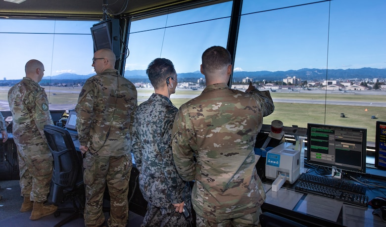 Senior Airman Kenyan Francis, 374th Operations Support Squadron air traffic controller, monitors flightline activity with Koku-Jieitai Tech. Sgt. Shinichi Ishimoto, Air Traffic Control Group air traffic controller assigned with Komatsu Air Base, Japan, from the air traffic control tower, Oct. 23, 2019, at Yokota Air Base.
