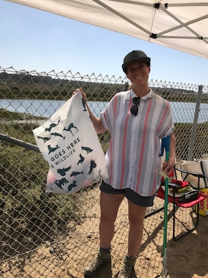 Tiffany Armenta holds up a bag of trash she collected during Coastal Cleanup Day Sept. 21 at the Santa Ana River Marsh in Newport Beach, California.