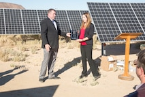 (Left) Steven Smith, vice president, Energy Systems Group; presents Alicia Florez, Engineering Manager, Production Plant Barstow, Marine Depot Maintenance Command; with a plaque thanking her for her part in getting the10-acre solar photo voltaic installation aboard the Yermo Annex up and going. The solar farm was officially opened when Col. Craig Clemans, commanding officer, Marine Corps Logistics Base Barstow, Calif., cut the ribbon on the project Oct. 22. The new solar project is expected to save the base $26,000,000 over the 22-year life of the contract with ESG