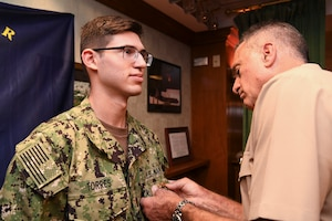 191023-N-KZ419-1040 NAVAL SUPPORT ACTIVITY BAHRAIN, Bahrain (Oct. 23, 2019) Rear Adm. Jack Buono, Superintendent of the U.S. Merchant Marine Academy, pins Ensign Ryan Torres with his Strategic Sealift Officer Warfare Insignia during after a tour of the Naval Coordination and Guidance for Shipping (NCAGS) facilities. The U.S. Naval Forces Central Command (NAVCENT) NCAGS team has recently amplified their support to the region in support of Operation Sentinel, a multinational maritime security effort designed to increase surveillance of key waterways in the Middle East to ensure freedom of navigation. (U.S. Navy photo by Mass Communication Specialist 3rd Class Dawson Roth/Released)