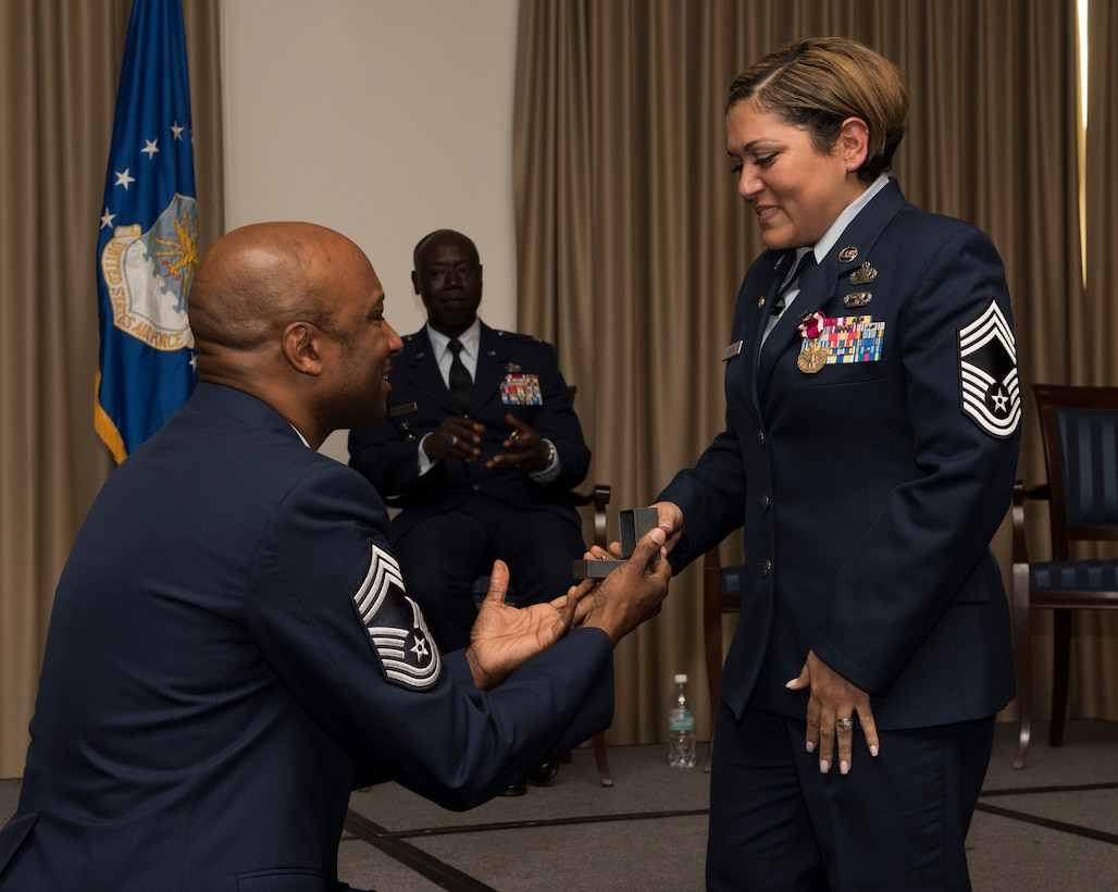Retired U.S. Air Force Chief Master Sgt. Robinson Joseph, left, former U.S. Air Forces in Europe – Air Forces Africa Chief Enlisted Manager for the Air Force Installation Contracting Center, proposes for the second time to his wife, retired Chief Master Sgt. Leenette Joseph, former USAFE Equal Opportunity functional manager, during their retirement ceremony on Ramstein Air Base, Germany, Oct. 25, 2019. Robinson said that he wanted to improve on his previous proposal, which was with an onion ring at a fast food restaurant.