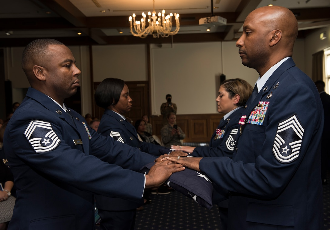 Retired U.S. Air Force Chief Master Sgt. Robinson Joseph, right, former U.S. Air Forces in Europe – Air Forces Africa Chief Enlisted Manager for the Air Force Installation Contracting Center, and his wife, retired Chief Master Sgt. Leenette Joseph, former USAFE Equal Opportunity functional manager, receive U.S. flags at their retirement ceremony on Ramstein Air Base, Germany, Oct. 25, 2019. During their careers, the Josephs served a combined 52 years, 21 assignments and 8 deployments.