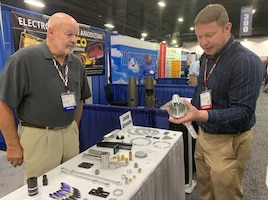 Phil Dicus, far right, DLA Troop Support Industrial Hardware employee speaks to a vendor at the Design-2-Part Show Oct. 23-24 in Oaks, Pennsylvania.