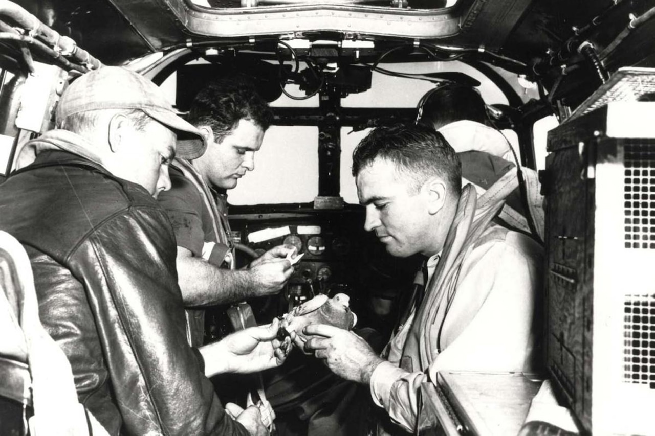 Soldiers sitting in a cockpit wearing World War II-era cold-weather flying clothes hold a pigeon.