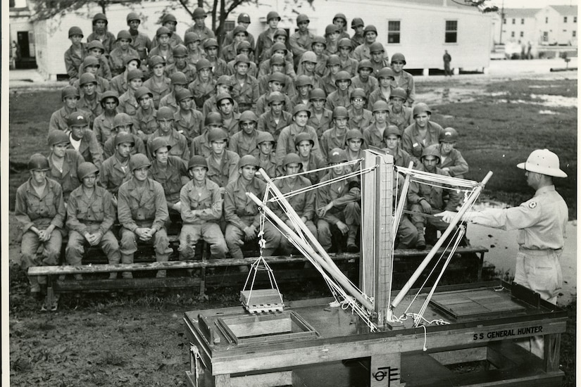 Soldiers sitting in bleachers watch a soldier use a wooden model of a crane to demonstrate how ships are loaded.