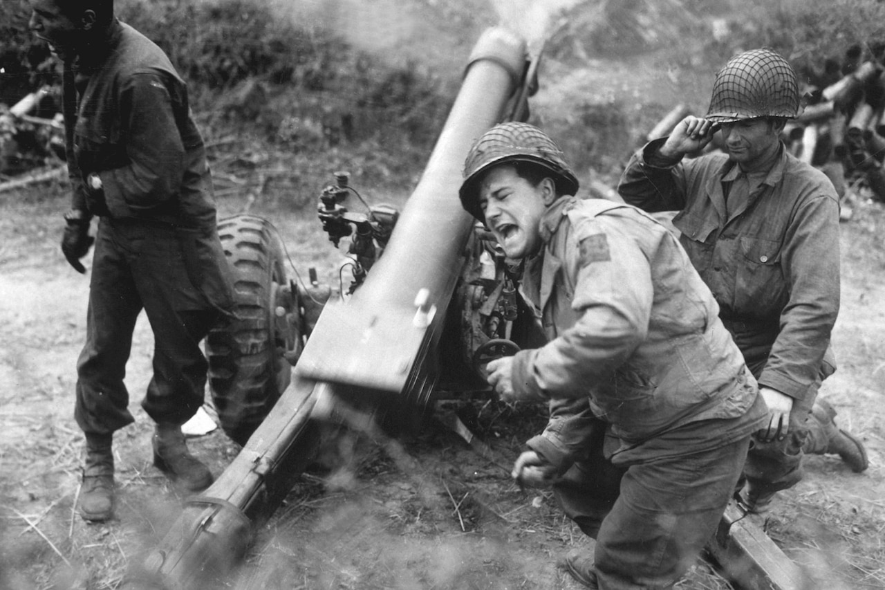 A soldier grimaces while firing an artillery piece.