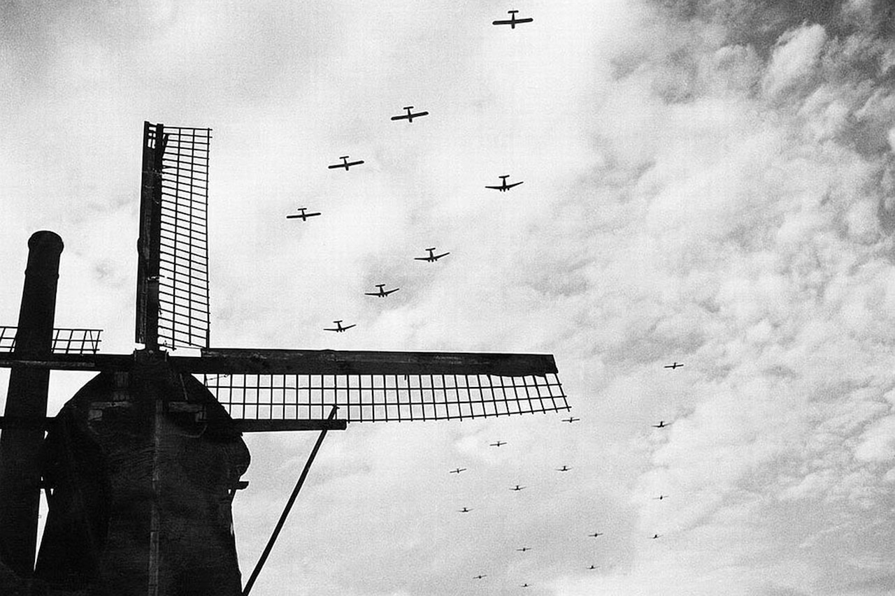 Aircraft fly over a windmill.