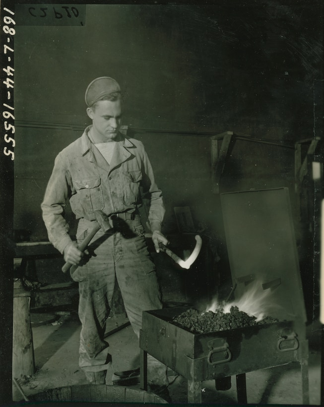 A soldier with a hammer in one hand holds a glowing hot metal bar over coals.