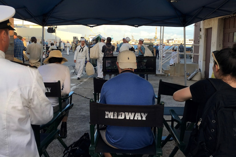 A group of people sit in chairs watching  the filming of a movie.