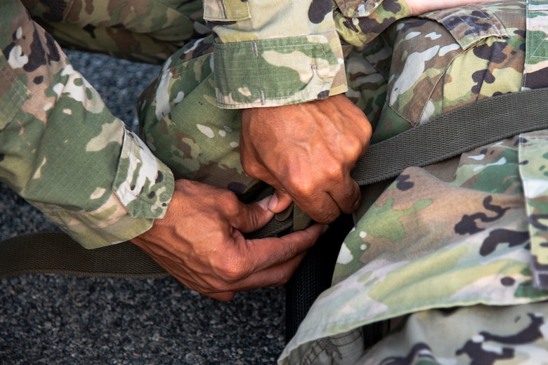 An Airmen with the 23d Medical Group (MDG) tightens litter straps during litter-carry training Oct. 25, 2019, at Moody Air Force Base, Ga. The 23d MDG conducted the training in preparation for the upcoming Thunder Over South Georgia Open House. Airmen practiced litter-carry movements and commands to ensure they have the appropriate skills in the case of an emergency. (U.S. Air Force photo by Airman 1st Class Taryn Butler)