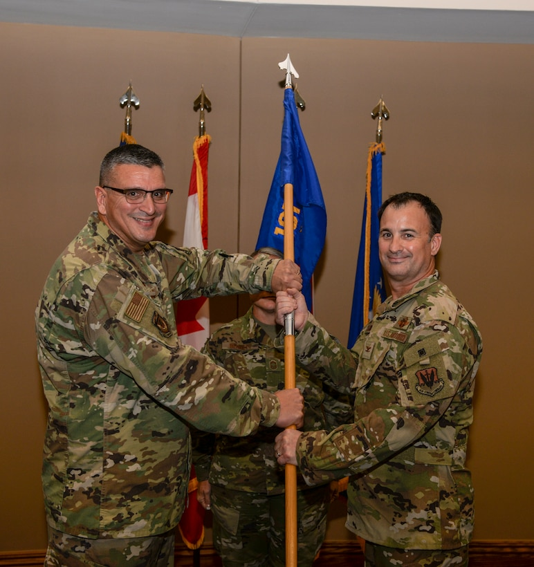 Col. Michael Valle, Assistant Adjutant General-Air and Florida Air National Guard commander, passes the ceremonial flag to Col. Matthew Jones, during the 101st Air and Space Group assumption of command ceremony held on the 601st Air Operations Center operations floor at Tyndall Air Force Base, Fla. on Oct. 25, 2019.