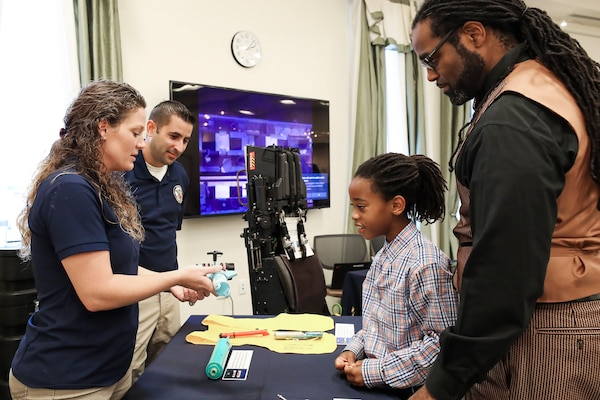 NSWC IHEODTD Acquisition Management Specialist Jessica Schombs and NSWC IHEODTD Equipment Specialist Nick Schombs of the CAD/PAD Division explain the components of an ejection seat to Antwan Proctor and his eight-year-old son Antwan Proctor, Jr. at the STEM Fest event held at Waldorf West Public Library, Oct. 26.
