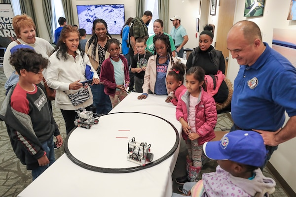 NSWC IHEODTD engineer John Kilikewich of the CAD/PAD Division looks on as students and parents watch Lego robots autonomously sumo wrestle at the STEM Fest event held at Waldorf West Public Library, Oct. 26 .  (U.S. Navy photo by Matthew Poynor)