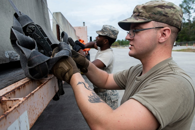 Senior Airman Maxwell Cisneros, 23d Logistics Readiness Squadron (LRS) ground transportation operator, secures cement barriers for transportation Oct. 25, 2019, at Moody Air Force Base, Ga. The 23d LRS Airmen used cement barriers to close off the HC-130J Combat King II ramp for air show parking and to protect Moody's assets and personnel. (U.S. Air Force photo by Airman Azaria E. Foster)