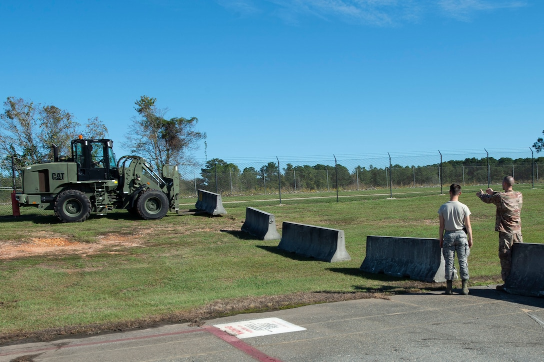 Airmen assigned to the 23d Logistics Readiness Squadron (LRS) place cement barriers on the flightline Oct. 28, 2019, at Moody Air Force Base, Ga. The 23d LRS Airmen used cement barriers to close off the HC-130J Combat King II ramp for air show parking and to protect Moody's assets and personnel. (U.S. Air Force photo by Airman Azaria E. Foster)