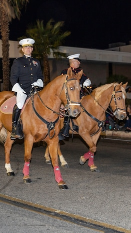 Colonel Craig C. Clemans (left), commanding officer of Marine Corps Logistics Base Barstow, and Sgt. Maj. Sergio MartinezRuiz, base sergeant major, ride in the Kiwanis Club's 87th annual Mardi Gras Parade in Barstow, Calif., Oct. 26. (U.S. Marine Corps photo by Jack J. Adamyk)