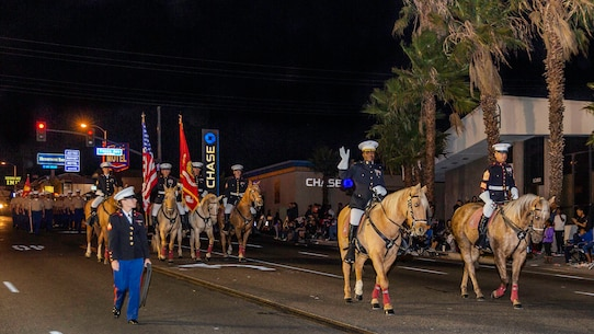 Major Earnest Robinson (middle-right), Headquarters Company Commanding Officer, and 1st Sgt. Enrique De Anda (right), HQCo first sergeant., ride ahead of the Marine Corps Mounted Color Guard and marching Headquarters Company Marines in the Kiwanis Club's 87th annual Mardi Gras Parade in Barstow, Calif., Oct. 26. (U.S. Marine Corps photo by Jack J. Adamyk)