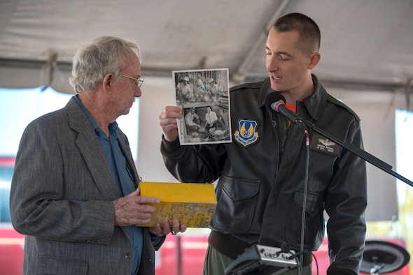 Lt. Col. Charles McNiel, 746th Test Squadron commander, shows a photo of Grady Nicholson, a former 46th Test Group engineer, during a 746th TS 60th anniversary event, Oct. 25, 2019, on Holloman Air Force Base, N.M. The photo shows a picture of Nicholson burying the same time capsule they opened for the anniversary event. (U.S. Air Force photo by Staff Sgt. Christine Groening)