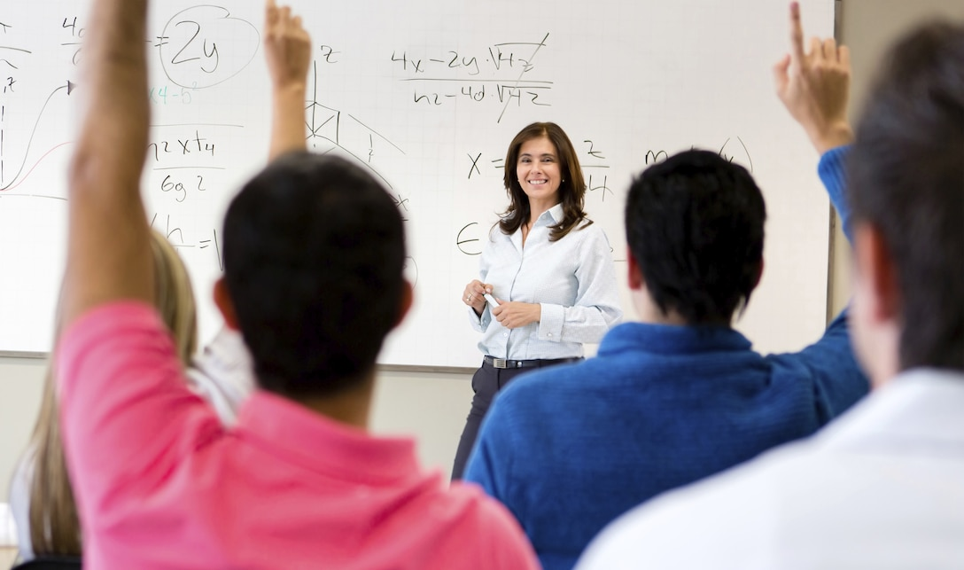 A teacher stands in front of a whiteboard as students raise their hands to answer her question.