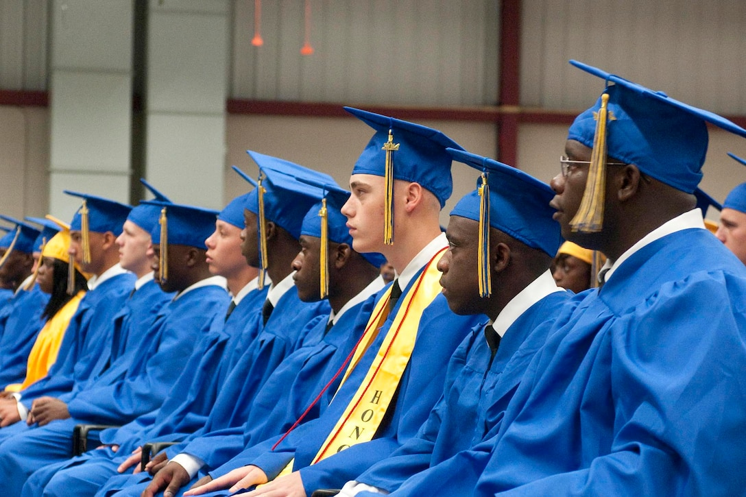 Graduates wearing caps and gowns are seated in a row.