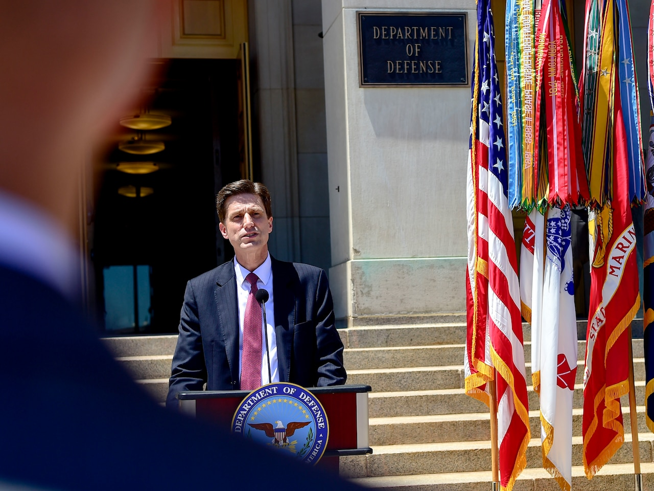 A man speaks into a microphone on a podium that has a Defense Department seal. The U.S. flag is to his right.