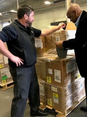 Two men look at a pallet of boxes
